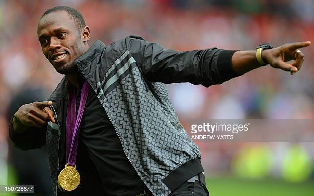Manchester United supporter and Jamaican Olympic sprint champion Usain Bolt from Jamaica walks onto the pitch with his gold medals before the English...
