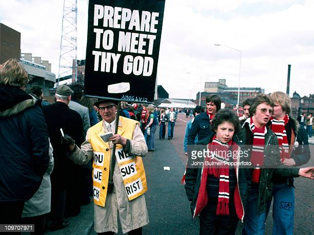 Manchester United supporters walk past an evangelist who is carrying a placard with a biblical quotation from Amos chapter 4 verse 12 'Prepare to...