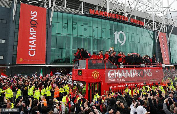Manchester United supporters welcome a bus carrying the players and officials at Old Trafford in Manchester north west England on May 30 2011 as the...