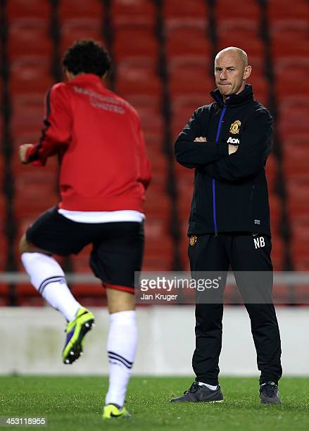 Manchester United U21 Manager Nicky Butt looks on as Fabio Da Silva warms up during the Barclays U21 Premier League match between Blackburn U21 and...