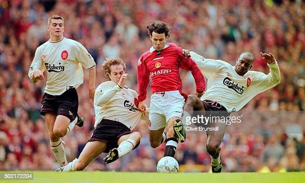 Manchester United winger Ryan Giggs is challenged by Jason McAteer and Michael Thomas as Dominic Matteo looks on during the FA Premier League match...
