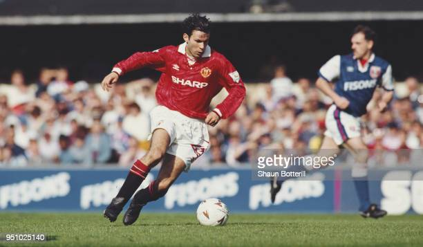 Manchester United winger Ryan Giggs on the ball as Town defender John Wark of Ipswich looks on during a Premiership match at Portman Road on May 1,...