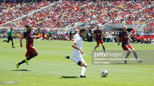 Manchester United's Adnan Januzaj carries the ball against FC Barcelona's Jordi Alba and Jeremy Mathieu in the second half during the Guinness...