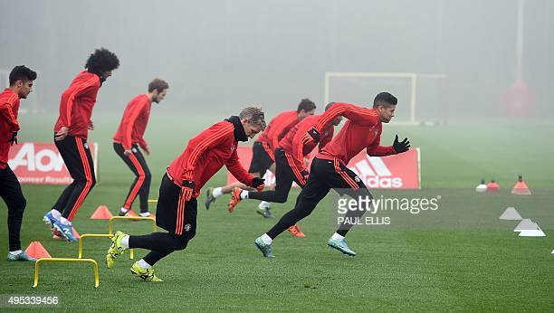 Manchester United's Argentinian defender Marcos Rojo and Manchester United's German midfielder Bastian Schweinsteiger run during a training session...