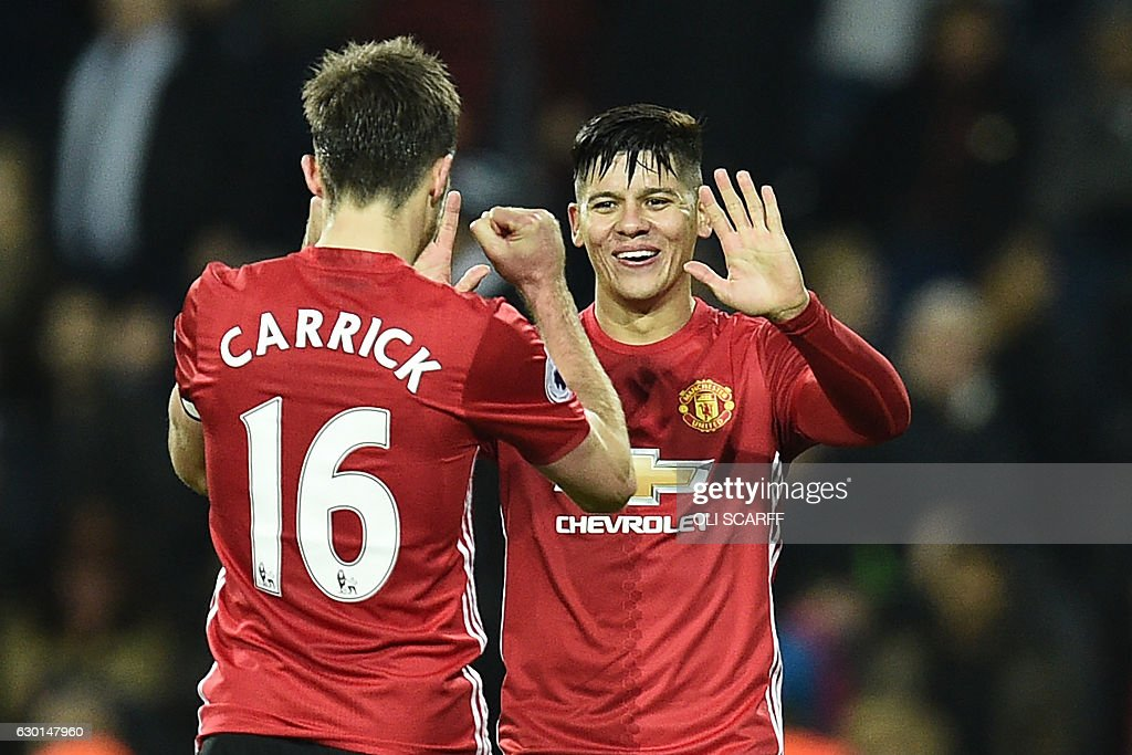 Manchester United's Argentinian defender Marcos Rojo (R) and Manchester United's English midfielder Michael Carrick (L) celebrate on the pitch after the English Premier League football match between West Bromwich Albion and Manchester United at The Hawthorns stadium in West Bromwich, central England, on December 17, 2016. Manchester United won the game 2-0. / AFP / Oli SCARFF / RESTRICTED TO EDITORIAL USE. No use with unauthorized audio, video, data, fixture lists, club/league logos or 'live' services. Online in-match use limited to 75 images, no video emulation. No use in betting, games or single club/league/player publications. /