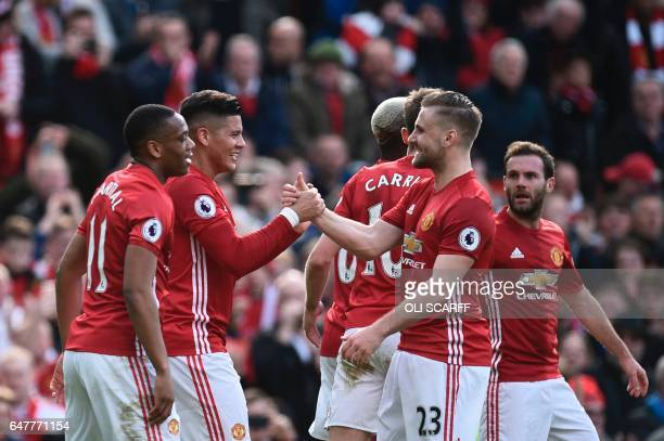 Manchester United's Argentinian defender Marcos Rojo celebrates with Manchester United's English defender Luke Shaw and teammates after scoring the...