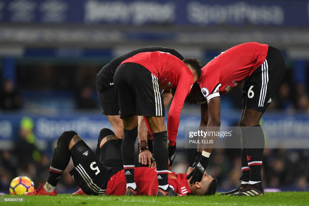 TOPSHOT - Manchester United's Argentinian defender Marcos Rojo receives medical attention during the English Premier League football match between Everton and Manchester United at Goodison Park in Liverpool, north west England on January 1, 2018. / AFP PHOTO / Paul ELLIS / RESTRICTED TO EDITORIAL USE. No use with unauthorized audio, video, data, fixture lists, club/league logos or 'live' services. Online in-match use limited to 75 images, no video emulation. No use in betting, games or single club/league/player publications. /