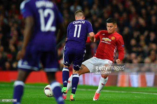 Manchester United's Argentinian defender Marcos Rojo takes a knock to his knee in a challenge with Anderlecht's Romanian midfielder Alexandru Chipciu...