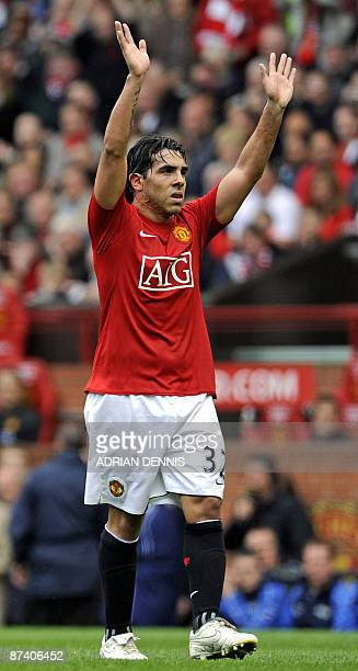 Manchester United's Argentinian forward Carlos Tevez waves to the crowd as he leaves the pitch after being substituted during the English Premier...