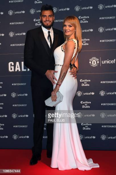 Manchester United's Argentinian goalkeeper Sergio Romero and his wife Eliana Guercio pose on the red carpet upon arrival to attend the United for...