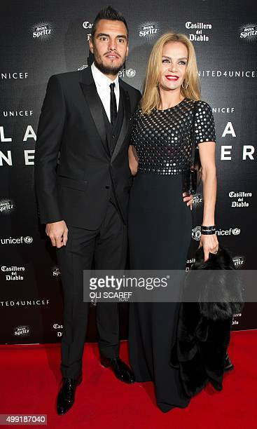 Manchester United's Argentinian goalkeeper Sergio Romero and his wife Eliana Guercio pose for pictures on the red carpet as they arrive to attend the...