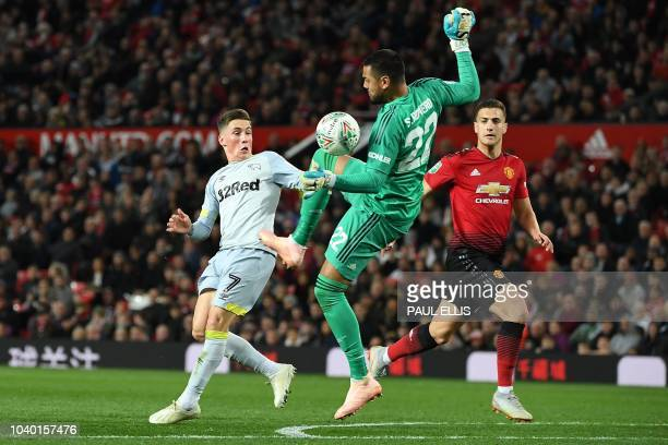 Manchester United's Argentinian goalkeeper Sergio Romero handball's the ball as he clashes with Derby's Welsh midfielder Harry Wilson during the...