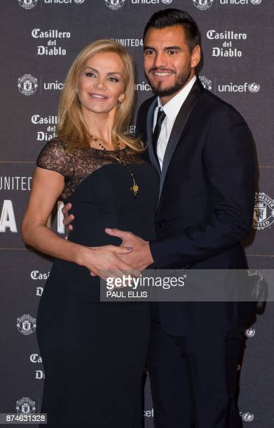 Manchester United's Argentinian goalkeeper Sergio Romero poses on the red carpet with Eliana Guercio as he arrives to attend the United for UNICEF...