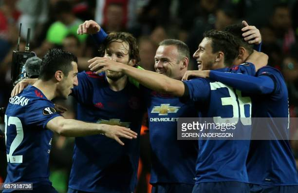 Manchester United's Armenian midfielder Henrikh Mkhitaryan Manchester United's English striker Wayne Rooney and teammates celebrate after they won...