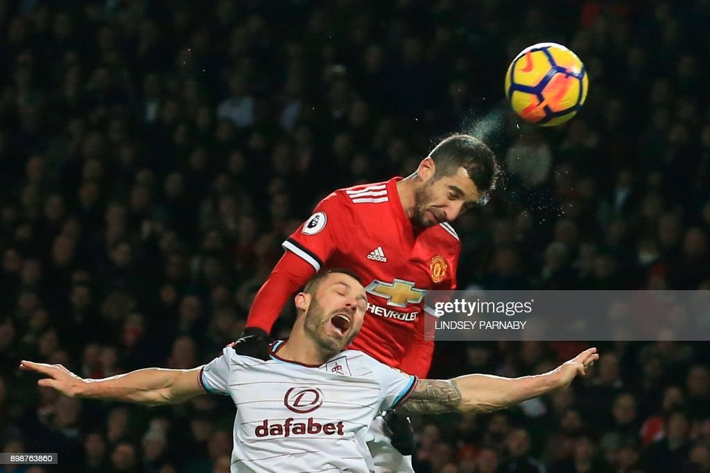 Manchester United's Armenian midfielder Henrikh Mkhitaryan (R) out-jumps Burnley's English-born Scottish defender Phil Bardsley (L) during the English Premier League football match between Manchester United and Burnley at Old Trafford in Manchester, north west England, on December 26, 2017. / AFP PHOTO / Lindsey PARNABY / RESTRICTED TO EDITORIAL USE. No use with unauthorized audio, video, data, fixture lists, club/league logos or 'live' services. Online in-match use limited to 75 images, no video emulation. No use in betting, games or single club/league/player publications. /