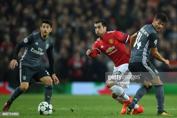 Manchester United's Armenian midfielder Henrikh Mkhitaryan vies with Benfica's Portuguese striker Diogo Goncalves during the UEFA Champions League...