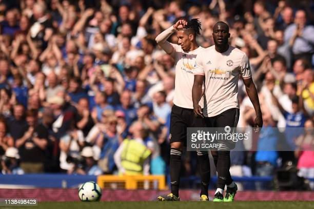 Manchester United's Belgian forward Romelu Lukaku and Manchester United's English defender Chris Smalling react after Everton's third goal during the...