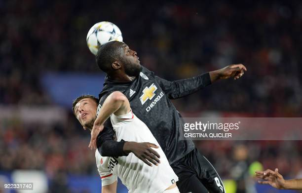 Manchester United's Belgian forward Romelu Lukaku jumps for the ball with Sevilla's French defender Clement Lenglet during the UEFA Champions League...
