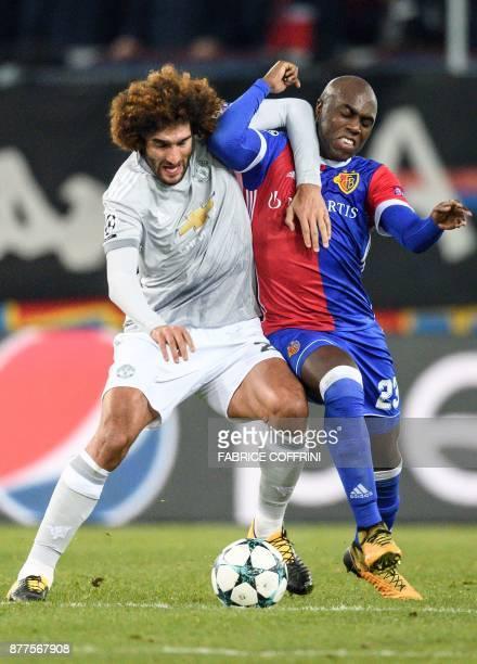 Manchester United's Belgian midfielder Marouane Fellaini and Basel's Colombian defender Eder Balanta vie for the ball during the UEFA Champions...