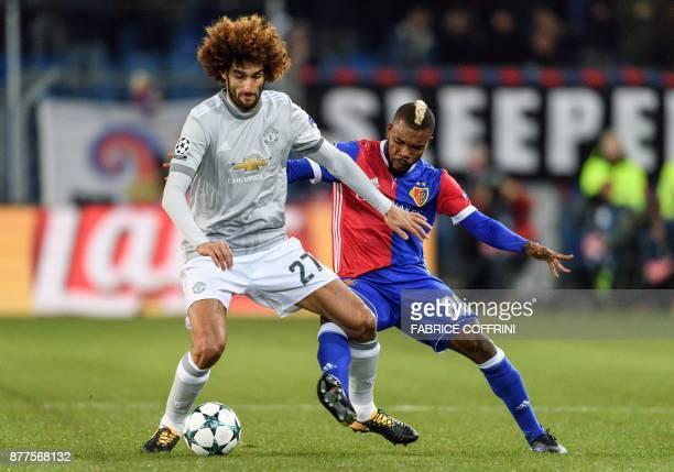 Manchester United's Belgian midfielder Marouane Fellaini Basel's Ivorian midfielder Geoffroy Serey Die vie for the ball during the UEFA Champions...