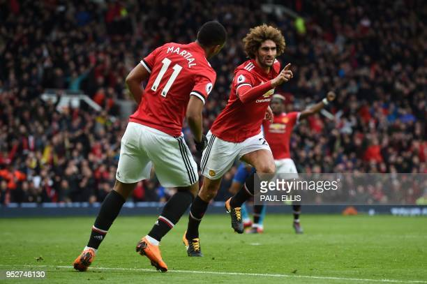 Manchester United's Belgian midfielder Marouane Fellaini celebrates with teammates after scoring their late second goal during the English Premier...