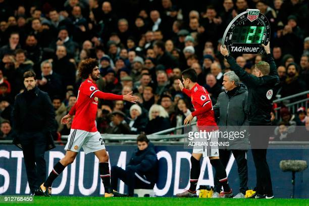 Manchester United's Belgian midfielder Marouane Fellaini goes by Manchester United's Portuguese manager Jose Mourinho as he leaves the pitch...