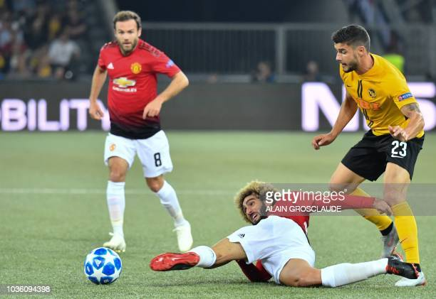 Manchester United's Belgian midfielder Marouane Fellaini plays the ball away from Young Boys Swiss defender Loris Benito during the UEFA Champions...