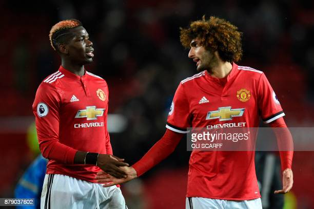 Manchester United's Belgian midfielder Marouane Fellaini shakes hands with Manchester United's French midfielder Paul Pogba during the English...