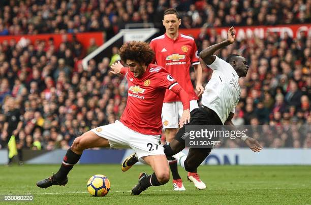 TOPSHOT Manchester United's Belgian midfielder Marouane Fellaini tackles Liverpool's Senegalese midfielder Sadio Mane who goes down in the challenge...