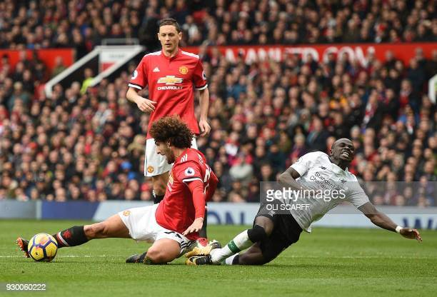 TOPSHOT Manchester United's Belgian midfielder Marouane Fellaini tackles Liverpool's Senegalese midfielder Sadio Mane who goes down in the challenge...