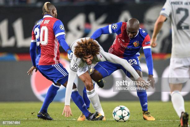 TOPSHOT Manchester United's Belgian midfielder Marouane Fellaini vies for the ball with Basel's Ivorian midfielder Geoffroy Serey Die and Basel's...