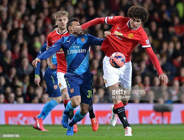Manchester United's Belgian midfielder Marouane Fellaini vies with Arsenal's French midfielder Francis Coquelin during the FA Cup quarterfinal...