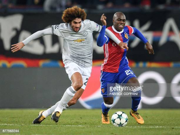 Manchester United's Belgian midfielder Marouane Fellaini vies with Basel's Colombian defender Eder Balanta during the UEFA Champions League Group A...