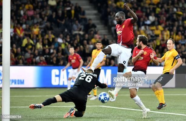 Manchester United's Belgian striker Romelu Lukaku and teammate Spanish midfielder Juan Mata fight for the ball with Young Boys Swiss goalkeeper David...