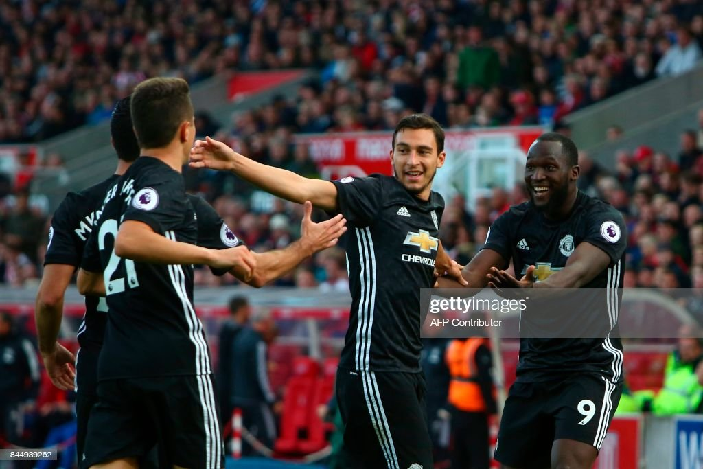Manchester United's Belgian striker Romelu Lukaku (R) celebrates scoring their second goal with teammates Manchester United's Italian defender Matteo Darmian (C), Manchester United's Armenian midfielder Henrikh Mkhitaryan (2L) and Manchester United's Spanish midfielder Ander Herrera (L) during the English Premier League football match between Stoke City and Manchester United at the Bet365 Stadium in Stoke-on-Trent, central England on September 9, 2017. / AFP PHOTO / Geoff CADDICK / RESTRICTED TO EDITORIAL USE. No use with unauthorized audio, video, data, fixture lists, club/league logos or 'live' services. Online in-match use limited to 75 images, no video emulation. No use in betting, games or single club/league/player publications. /