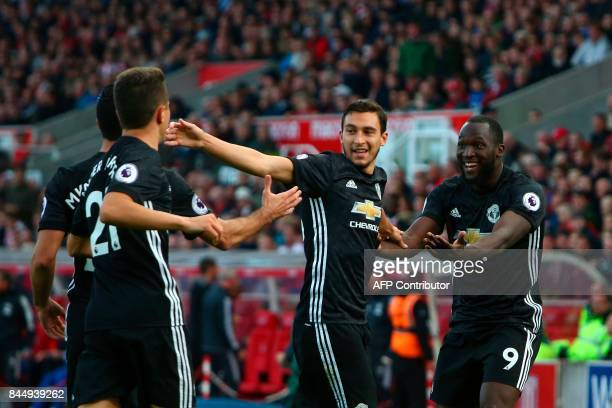 Manchester United's Belgian striker Romelu Lukaku celebrates scoring their second goal with teammates Manchester United's Italian defender Matteo...
