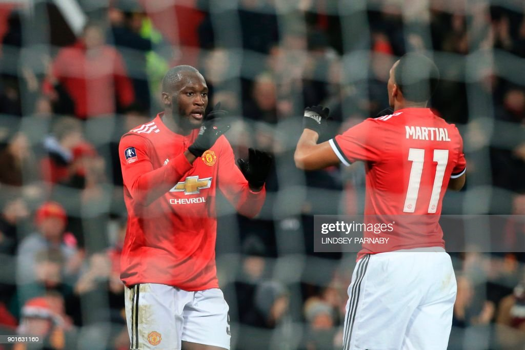 Manchester United's Belgian striker Romelu Lukaku (L) celebrates scoring their second goal with Manchester United's French striker Anthony Martial (R) during the English FA Cup third round football match between Manchester United and Derby County at Old Trafford in Manchester, north west England, on January 5, 2018. / AFP PHOTO / Lindsey PARNABY / RESTRICTED TO EDITORIAL USE. No use with unauthorized audio, video, data, fixture lists, club/league logos or 'live' services. Online in-match use limited to 75 images, no video emulation. No use in betting, games or single club/league/player publications. /
