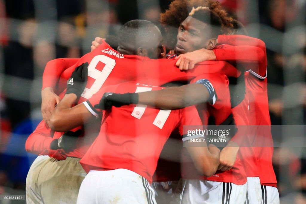 Manchester United's Belgian striker Romelu Lukaku (L) celebrates scoring their second goal with team-mates during the English FA Cup third round football match between Manchester United and Derby County at Old Trafford in Manchester, north west England, on January 5, 2018. / AFP PHOTO / Lindsey PARNABY / RESTRICTED TO EDITORIAL USE. No use with unauthorized audio, video, data, fixture lists, club/league logos or 'live' services. Online in-match use limited to 75 images, no video emulation. No use in betting, games or single club/league/player publications. /