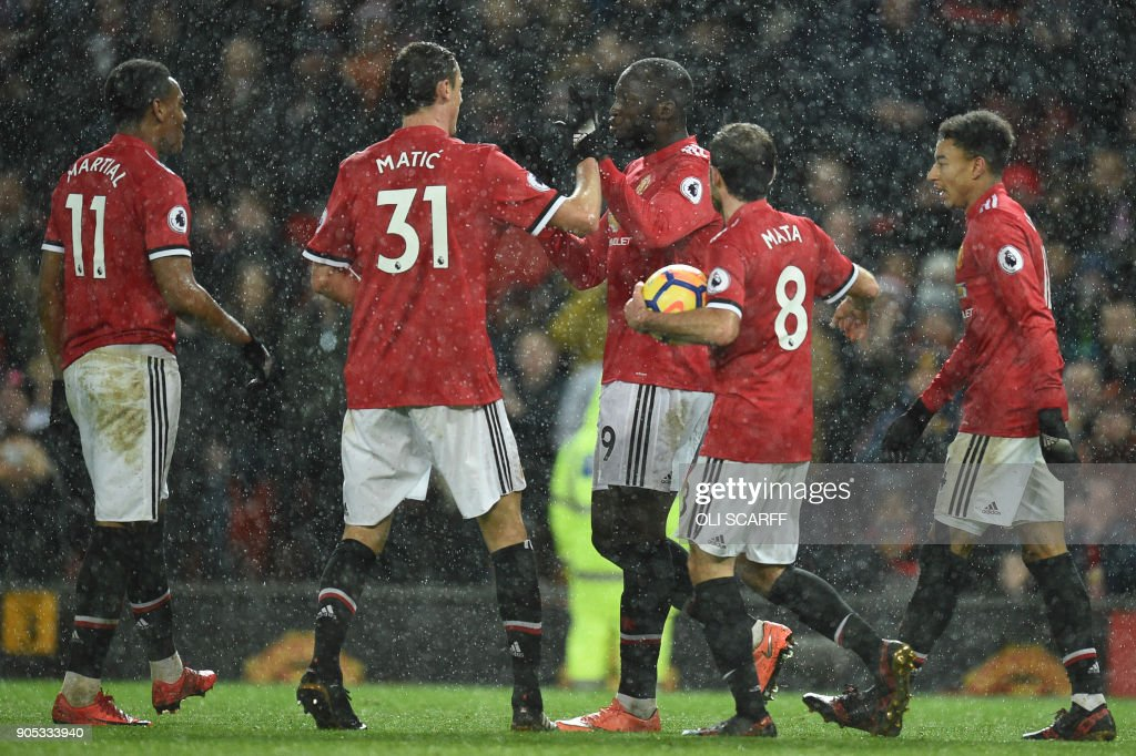 Manchester United's Belgian striker Romelu Lukaku (C) celebrates scoring their third goal during the English Premier League football match between Manchester United and Stoke City at Old Trafford in Manchester, north west England, on January 15, 2018. / AFP PHOTO / Oli SCARFF / RESTRICTED TO EDITORIAL USE. No use with unauthorized audio, video, data, fixture lists, club/league logos or 'live' services. Online in-match use limited to 75 images, no video emulation. No use in betting, games or single club/league/player publications. /