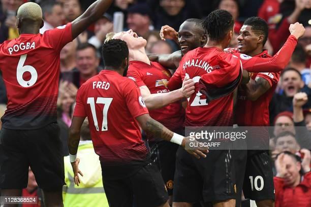 Manchester United's Belgian striker Romelu Lukaku celebrates with teammates after scoring their third goal during the English Premier League football...
