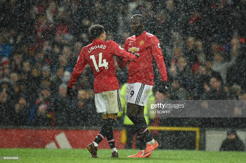 Manchester United's Belgian striker Romelu Lukaku (R) celebrates with Manchester United's English midfielder Jesse Lingard (L) after scoring their third goal during the English Premier League football match between Manchester United and Stoke City at Old Trafford in Manchester, north west England, on January 15, 2018. / AFP PHOTO / Oli SCARFF / RESTRICTED TO EDITORIAL USE. No use with unauthorized audio, video, data, fixture lists, club/league logos or 'live' services. Online in-match use limited to 75 images, no video emulation. No use in betting, games or single club/league/player publications. /