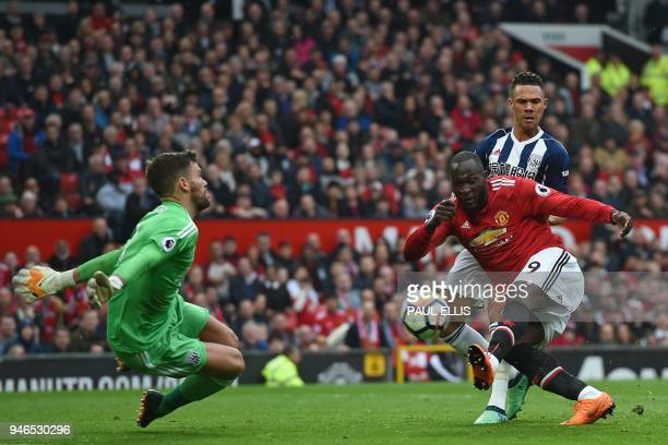 Manchester United's Belgian striker Romelu Lukaku has this shot saved by West Bromwich Albion's English goalkeeper Ben Foster during the English...