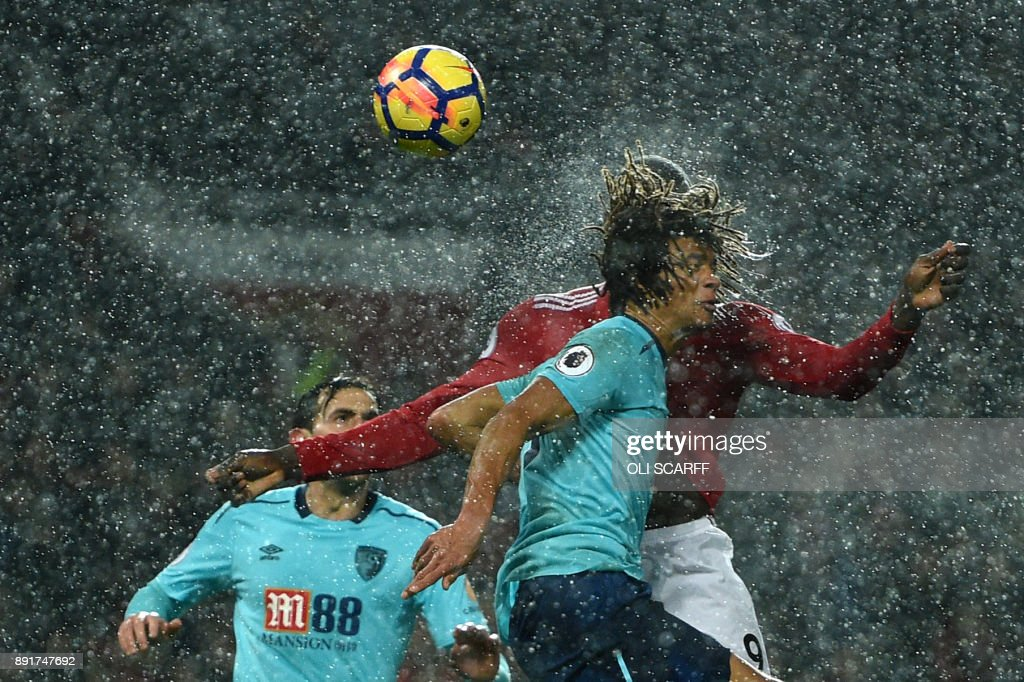 TOPSHOT - Manchester United's Belgian striker Romelu Lukaku (R) heads the ball past Bournemouth's Dutch defender Nathan Ake to score during the English Premier League football match between Manchester United and Bournemouth at Old Trafford in Manchester, north west England, on December 13, 2017. / AFP PHOTO / Oli SCARFF / RESTRICTED TO EDITORIAL USE. No use with unauthorized audio, video, data, fixture lists, club/league logos or 'live' services. Online in-match use limited to 75 images, no video emulation. No use in betting, games or single club/league/player publications. /