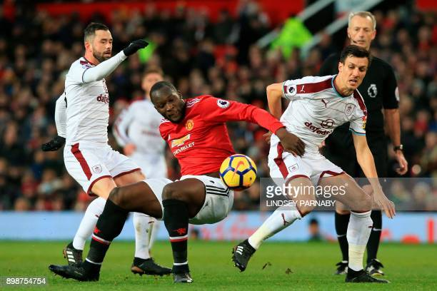 Manchester United's Belgian striker Romelu Lukaku is challenged by Burnley's Belgian midfielder Steven Defour and Burnley's English midfielder Jack...