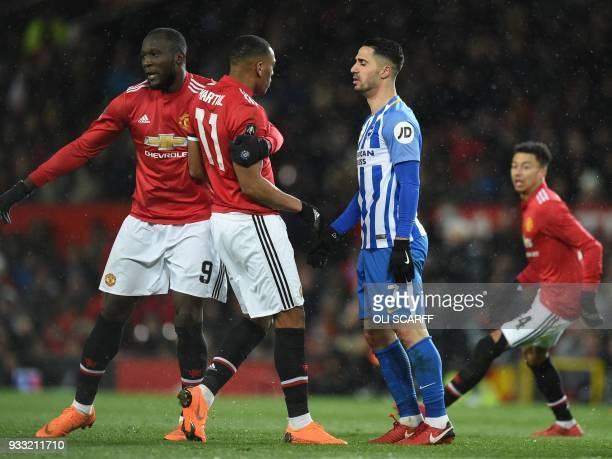 Manchester United's Belgian striker Romelu Lukaku pulls Manchester United's French striker Anthony Martial from a dispute with Brighton's Israeli...