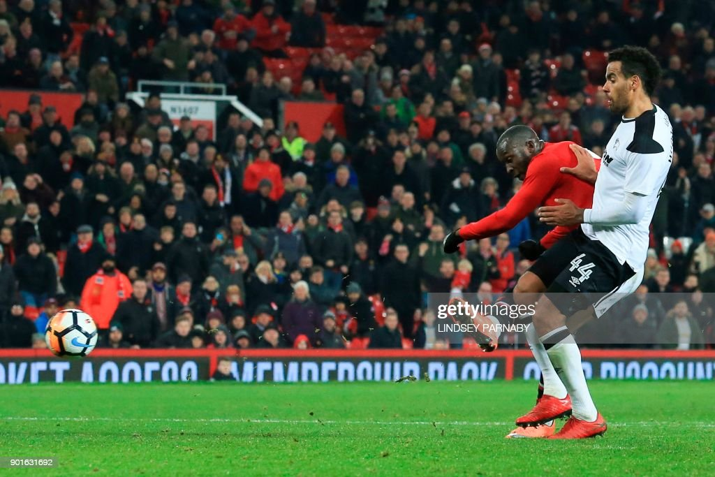 Manchester United's Belgian striker Romelu Lukaku (L) scores their second goal during the English FA Cup third round football match between Manchester United and Derby County at Old Trafford in Manchester, north west England, on January 5, 2018. / AFP PHOTO / Lindsey PARNABY / RESTRICTED TO EDITORIAL USE. No use with unauthorized audio, video, data, fixture lists, club/league logos or 'live' services. Online in-match use limited to 75 images, no video emulation. No use in betting, games or single club/league/player publications. /