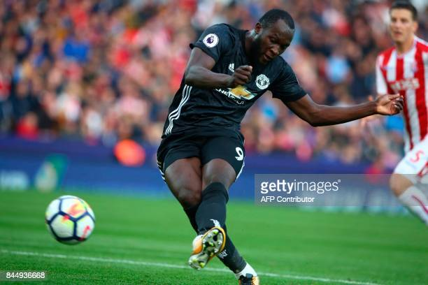 Manchester United's Belgian striker Romelu Lukaku takes a shot that rebounds of Stoke City's English goalkeeper Jack Butland which leads to...