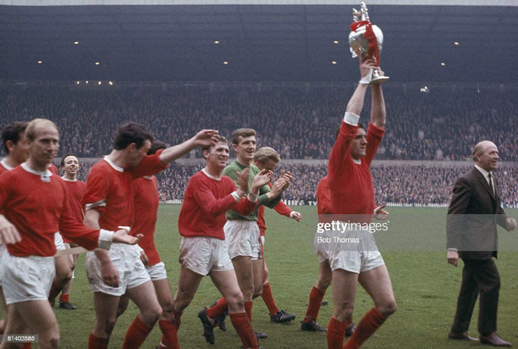 Manchester United's Bill Foulkes holds the 1st Division Championship trophy aloft as their manager, Matt Busby, leads the team on a lap of honour around Old Trafford at the end of the 1966-67 season. Also shown in the image (from the left) are Bobby Charlton, Nobby Stiles, David Sadler, Pat Crerand, Alex Stepney and Denis Law. (Photo by Bob Thomas/Getty Images).