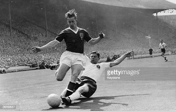 Manchester United's Bobby Charlton being tackled by T Banks the Bolton Wanderers left back during the FA Cup Final at Wembley Bolton won 20