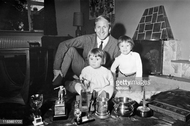 Manchester United's Bobby Charlton shows off his many trophies that he has won to his two children Andrea and Suzanne ay their home at Lymm Cheshire...